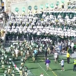 CSU Football team runs over to the marching band