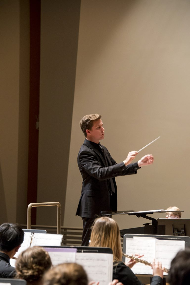 Spencer Poston conducts the Middle School Outreach Ensemble band